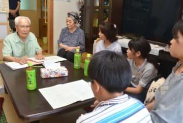 自宅を訪問した親子に自身の経験を語る福仲功さん(左)=鹿屋市の星塚敬愛園