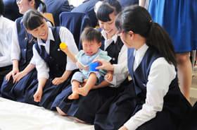 泣いている赤ちゃんをあやす女子生徒