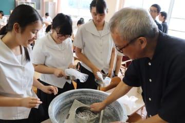メッセージカードに同封する折り鶴の灰をふるいにかける太田さん(右)と生徒=波佐見高