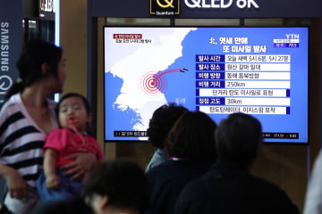 7月31日、ソウル市内で、北朝鮮が発射した飛翔体のニュースを見る市民ら(ゲッティ=共同)