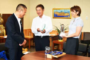 久喜邦康市長(左)にトロフィーを披露し、受賞を報告した肥土伊知郎社長(中央)と吉川由美さん=7月31日午後2時ごろ、秩父市役所