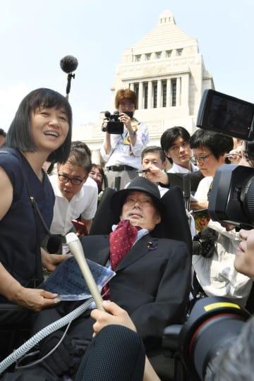 初登院し、国会議事堂を背に、介助者(左)と共に記者の質問に答えるれいわ新選組の舩後靖彦氏=1日午前9時35分
