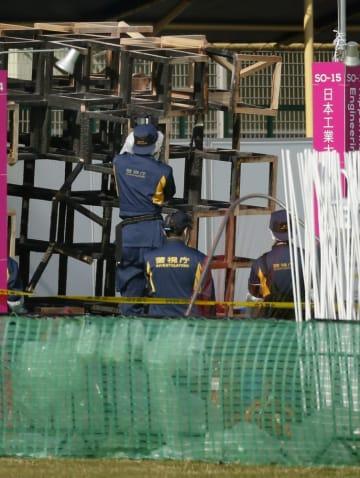 東京・明治神宮外苑のイベント会場で、男児が死亡した火災現場の木製オブジェを調べる捜査員=2016年11月7日午前9時50分