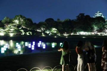 沢の池に灯籠を浮かべ、幻想的ムードを演出した後楽園。右奥は岡山城