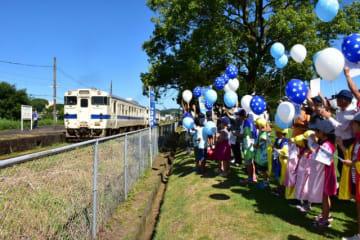 JR吉都線の運行再開を祝う沿線住民や園児ら=1日午前8時59分、小林市・JR小林駅前の市中央ふれあい広場