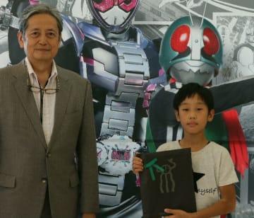 仮面ライダー展の観覧者1万人目になった挟間郁君(右)と大分市美術館の菅章館長