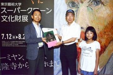 山埜浩嗣館長(左)から記念品を受け取る1万人目の来場者=8月1日、福井県福井市の福井県立美術館