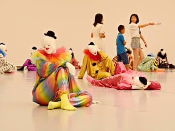 人間が24時間に行う45の振る舞いを表したピエロの人形が並ぶ会場を見て回る家族連れ=1日午前11時23分、名古屋市東区、愛知芸術文化センター