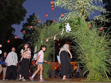 カヤで作られた輪をくぐって無病息災を願う参拝客たち=可児市土田、白鬚神社