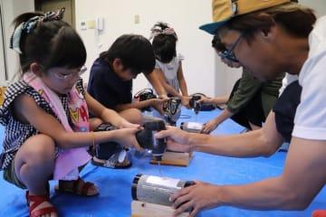 竹にドリルで穴を開け、竹あかり作りに挑戦する子どもたち=長崎市琴海村松町