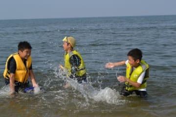 【海辺で水遊びを楽しむ子どもら=津市藤方で】