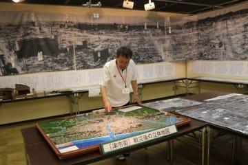 【戦災後の津市の写真や立体地図を置く展示会場=津市西丸之内の津リージョンプラザで】