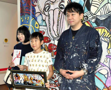 1万人目の入場者となり、石村さん(右)の作品を手に記念撮影する石川君(中央)