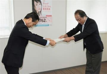 最低賃金改定の目安額を伝達される橋本眞・熊本地方最低賃金審議会長(右)=1日、熊本市西区