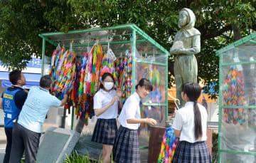 「ガラスのうさぎ」像に千羽鶴を飾る二宮高校の生徒ら=JR二宮駅前