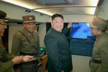 多連装ロケット砲の試射を視察する北朝鮮の金正恩朝鮮労働党委員長(中央)。3日付の労働新聞が掲載した(コリアメディア提供・共同)