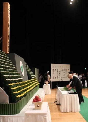 【戦没者追悼式で献花する遺族ら=津市一身田上津部田で】