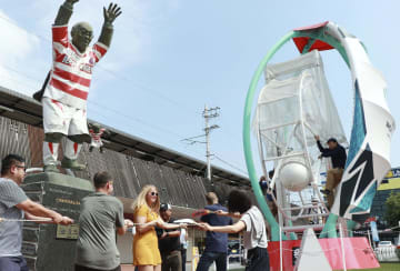 JR別府駅前で行われた、ラグビーボール形の巨大砂時計(右)の反転作業=3日午前、大分県別府市