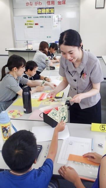 模擬紙幣を使い、業務部職員とお金のやりとりを体験する小学生 =かながわ信用金庫