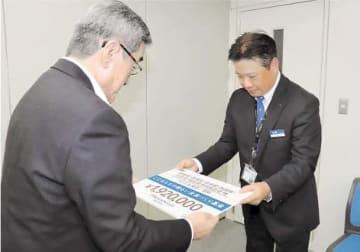 田村常務理事(左)に目録を手渡す谷川支社長