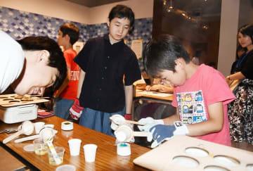 クレヨン作りに励む児童(右)=8月3日、福井県福井市の福井県立美術館