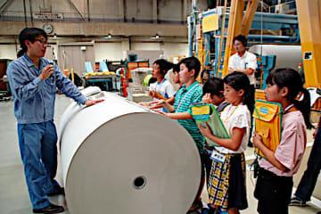 工場関係者(左)から新聞用紙の製造工程の説明を受ける子どもたち=3日、愛媛県四国中央市の大王製紙三島工場