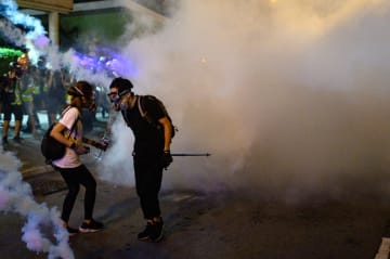 Protesters gather next to tear gas, outside of a police station in the Wong Tai Sin district of Hong Kong early on August 4, 2019, after arrested protesters were taken to the station in a police van. Photo: Philip Fong/AFP.