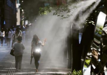 厳しい暑さの中、ドライミストの下を歩く人たち=4日午後、東京・丸の内