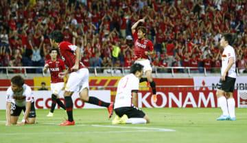 J1 浦和―名古屋 試合終了間際、同点ゴールを決め、ガッツポーズする浦和・関根(中央奥)。手前は肩を落とす名古屋イレブン=埼玉スタジアム