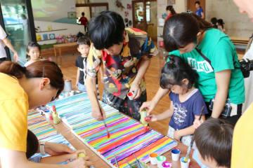 冨永ボンドさん(中央)と一緒にボンドアートに挑戦する児童ら=佐賀市水ヶ江のおへそこども園