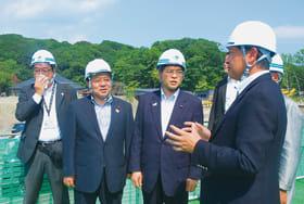 戸田安彦白老町長(右)から説明を受ける石井大臣(左から3人目)