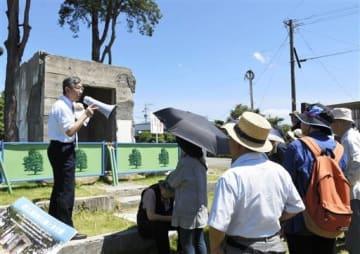 陸軍黒石原飛行場跡に立つ「奉安殿」について伊藤利明さん(左)の説明を受けるツアー参加者ら=4日、合志市