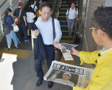 渋野選手の快挙を伝える山陽新聞の号外を受け取るJR岡山駅の利用客