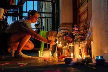 銃乱射事件の犠牲者の追悼集会でろうそくに火をともす人=4日、米中西部オハイオ州デートン(ロイター=共同)