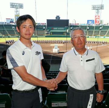 握手をする藤蔭の竹下大雅監督(左)、明徳義塾の馬淵史郎監督=甲子園球場