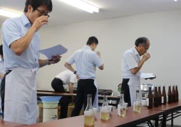 【新酒の利き酒をする審査員ら=松阪市日野町の同市市民活動センターで】