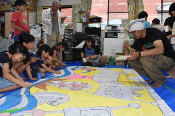 児童と色塗りに励むサニョさん(右)=長崎市、学童保育やまざとクラブ