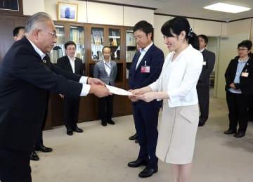 手交式に臨んだ八木局長(左)と越市長ら=大阪市中央区