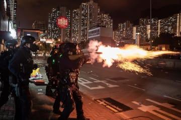 5日、香港のデモの最中に催涙ガスを発射する警官(ゲッティ=共同)