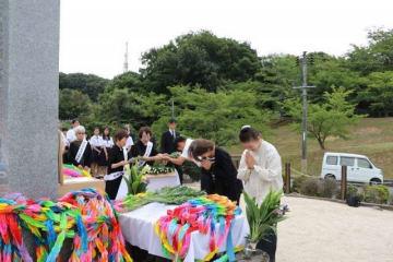 原爆犠牲者の供養塔に白菊の花を手向ける参列者