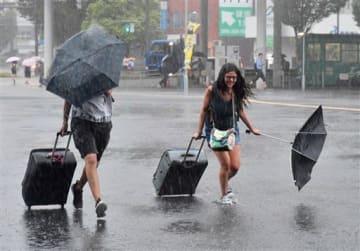 台風8号の接近で風雨が強まる中、急いでJR熊本駅に向かう人たち=6日午前8時15分ごろ、熊本市西区春日(池田祐介)