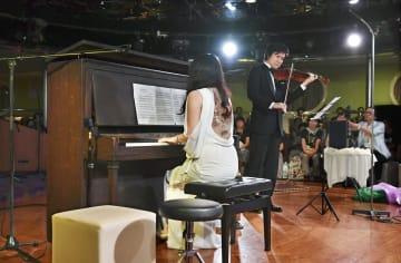 停泊中の船で演奏するピアニストの萩原麻未さんとバイオリニストの成田達輝さん=6日午後、広島市