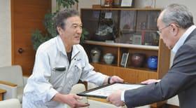 仁木副市長から感謝状を受け取る田村課長(左)
