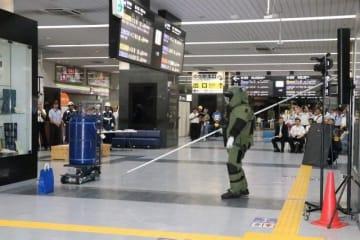 棒状の道具を手に、防護服を着て爆発物が入った紙袋に近寄る岡山県警機動隊員