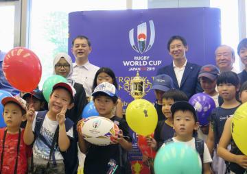 ラグビーW杯の優勝トロフィー「ウェブ・エリス・カップ」と記念撮影する児童ら=7日、文科省