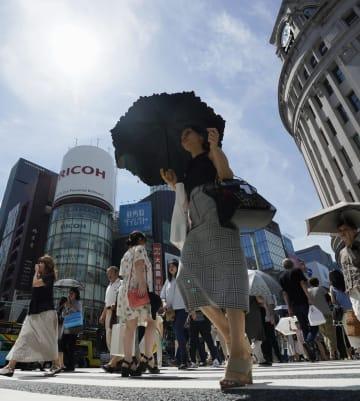 強い日差しが照りつける中、東京・銀座を行き交う人たち=7日午後