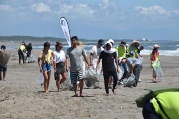 約1カ月後の大会本番を前に、会場となる宮崎市・木崎浜で清掃活動に汗を流すサーファーら=4日