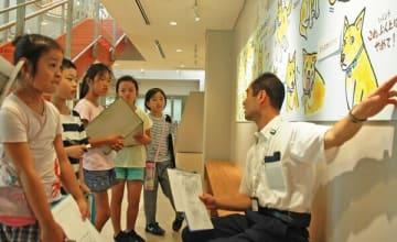 イラストパネルで、犬のボディーランゲージを学ぶ子どもたち=川崎市中原区の市動物愛護センター