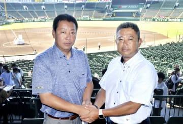 健闘を誓って握手する敦賀気比の東哲平監督(左)と富島の浜田登監督=甲子園