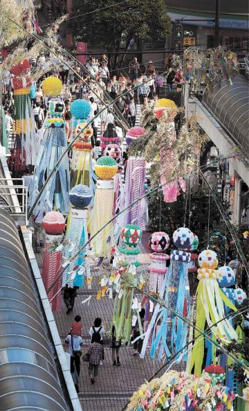商店街に飾り付けられた吹き流しの下を大勢の見物客が行き交う=7日午後4時すぎ、仙台市青葉区一番町4丁目